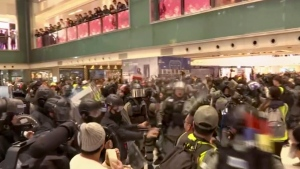 In this image made from video, police and protester scuffle at a shopping mall in Sha Tin district in Hong Kong, with shoppers watch from balconies above, Sunday, Dec. 15, 2019. The rally, which had a Christmas shopping theme, was the latest in a series of demonstrations, which have beset Hong Kong for more than six months.(AP Photo)