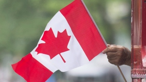 A man waves a flag during a Canada Day parade in Montreal, on July 1, 2018. (THE CANADIAN PRESS / Graham Hughes)