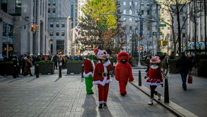 "In this Friday, Dec. 20, 2019 photo, costumed performers leave Rockefeller Center in New York. Some performers, who solicit tips from tourists from designated ""activity zones"" in Times Square, have been migrating to Rockefeller Center for the holiday season where no such zones exist. (AP Photo/Bebeto Matthews)"