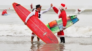 George Trosset Jr. and George Trosset, who started surfing in Santa and Christmas costumes ten years ago behind their house on Christmas Eve, high five each other during the 10th annual Surfing Santas event in Cocoa Beach, Fla., Tuesday, Dec. 24, 2019. The event has grown and now raises money for two local non profits - Grind for Life, which helps with financial assistance for cancer patients, and the Florida Surf Museum. (Malcolm Denemark/Florida Today via AP)