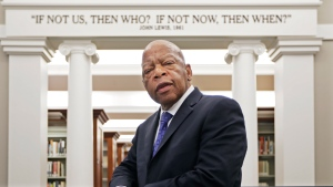 FILE - In this Nov. 18, 2016, file photo, U.S. Rep. John Lewis, D-Ga., poses for a photograph under a quote of his that is displayed in the Civil Rights Room in the Nashville Public Library in Nashville, Tenn.  (AP Photo/Mark Humphrey, File)