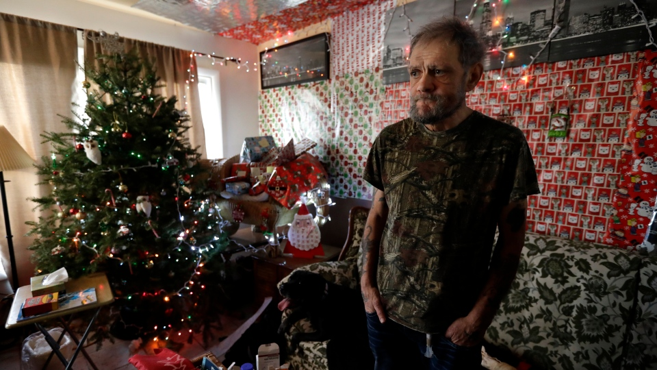 In this Friday, Dec. 20, 2019 photo, Bobby Goldberg stands in the living room at his home in suburban Chicago. Goldberg has filed a lawsuit claiming he was abused more than 1,000 times in multiple states and countries by the late Donald McGuire, a prominent American Jesuit priest who had close ties to Mother Teresa. (AP Photo/Nam Y. Huh)