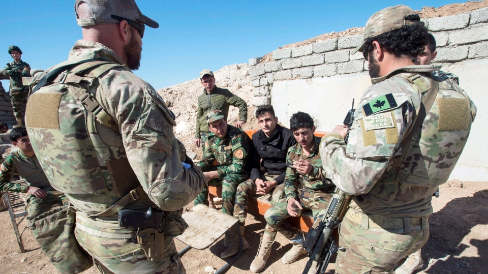 In this Feb. 20, 2017 file photo, Canadian special forces soldiers, left and right, speak with Kurdish Peshmerga fighters at an observation post, in northern Iraq. (Ryan Remiorz/The Canadian Press via AP, File)