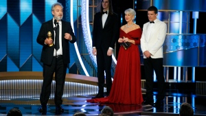 "This image released by NBC shows Sam Mendes accepting the award for best director for the film ""1917"" as presenters Antonio Banderas, right, and Helen Mirren look on at the 77th Annual Golden Globe Awards at the Beverly Hilton Hotel in Beverly Hills, Calif., on Sunday, Jan. 5, 2020. (Paul Drinkwater/NBC via AP)"