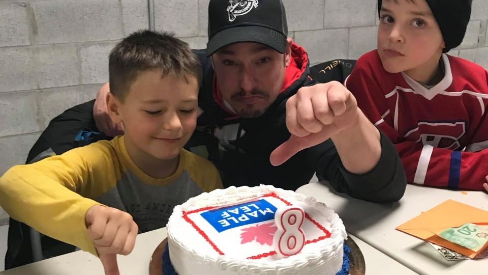 Eight-year-old Jacob Bertrand (left) poses with his father Mathieu Bertrand and a friend in a handout photo. His family ordered a Toronto Maple Leafs cake for Jacob's birthday and got a cake with a Maple Leaf Foods logo instead. THE CANADIAN PRESS/HO-Tania Levesque