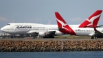In this Aug. 20, 2015 file photo, two Qantas planes taxi on the runway at Sydney Airport in Sydney, Australia. Some Asian airlines have rerouted flights to the Middle East to avoid Iranian airspace, amid escalated tensions over the United States' assassination of a prominent Iranian commander in Iraq. (AP Photo/Rick Rycroft, File)