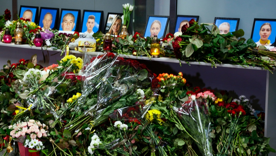Flowers and candles are placed in front of portraits of the flight crew members of the Ukrainian 737-800 plane that crashed on the outskirts of Tehran, at a memorial inside Borispil international airport outside Kyiv, Ukraine, Wednesday, Jan. 8, 2020. (AP Photo/Efrem Lukatsky)