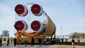 Security personnel walk with the core stage of NASA's Space Launch System rocket, that will be used for the Artemis 1 Mission, as it is moved to the Pegasus barge, at the NASA Michoud Assembly Facility where it was built, in New Orleans, Wednesday, Jan. 8, 2020. It will be transported to NASA's Stennis Space Center in Mississippi for its green run test. (AP Photo/Gerald Herbert)