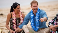 """In this Friday, Oct. 19, 2018 file photo Britain's Prince Harry and Meghan, Duchess of Sussex meet with a local surfing community group, known as OneWave, raising awareness for mental health and wellbeing in a fun and engaging way at Bondi Beach in Sydney, Australia. In a stunning declaration, Britain's Prince Harry and his wife, Meghan, said they are planning """"to step back"""" as senior members of the royal family and """"work to become financially independent."""" A statement issued by the couple Wednesday, Jan. 8, 2020 also said they intend to """"balance"""" their time between the U.K. and North America. (Dominic Lipinski/Pool via AP)"""