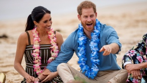 "In this Friday, Oct. 19, 2018 file photo Britain's Prince Harry and Meghan, Duchess of Sussex meet with a local surfing community group, known as OneWave, raising awareness for mental health and wellbeing in a fun and engaging way at Bondi Beach in Sydney, Australia. In a stunning declaration, Britain's Prince Harry and his wife, Meghan, said they are planning ""to step back"" as senior members of the royal family and ""work to become financially independent."" A statement issued by the couple Wednesday, Jan. 8, 2020 also said they intend to ""balance"" their time between the U.K. and North America. (Dominic Lipinski/Pool via AP)"