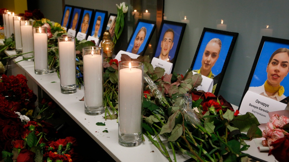 Flowers and candles are placed in front of portraits of the flight crew members of the Ukrainian 737-800 plane that crashed on the outskirts of Tehran, at a memorial inside Borispil international airport outside Kyiv, Ukraine, in this file photo from Wednesday, Jan. 8, 2020. (File/AP Photo/Efrem Lukatsky)