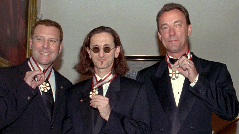 "Members of the rock group ""Rush"", Alex Lifeson, Geddy Lee, and Neil Peart (left to right) display their Order of Canada medals which were presented to them at a ceremony at Rideau Hall in Ottawa on Wednesday Feb. 2, 1997.  (CP PHOTO ARCHIVE-Jim Young)"