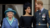 FILE - In this Tuesday, July 10, 2018 file photo Britain's Queen Elizabeth II, and Meghan the Duchess of Sussex and Prince Harry watch a flypast of Royal Air Force aircraft pass over Buckingham Palace in London. (AP Photo/Matt Dunham, File)