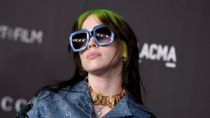 "FILE - This Nov. 2, 2019 file photo shows singer Billie Eilish at the 2019 LACMA Art and Film Gala in Los Angeles. Eilish is set to the sing the theme song for the upcoming James Bond film, becoming the youngest act to write and record a song for the iconic film franchise. Eilish, who turned 18 in December, recorded the song for the 25th Bond film, ""No Time to Die,"" which debuts in U.S. theaters on April 10. (Photo by Jordan Strauss/Invision/AP, File)"