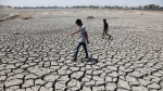 In this May 14, 2016, file photo, boys on their way to play cricket walk through a dried patch of Chandola Lake in Ahmadabad, India. The decade that just ended was by far the hottest ever measured on Earth, capped off by the second-warmest year on record, NASA and the National Oceanic and Atmospheric Administration reported Wednesday, Jan. 15, 2020. (AP Photo/Ajit Solanki, File)