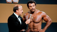 """In this undated photo provided by WWE, Inc., """"Mean"""" Gene Okerlund interviews Rocky """"Soul Man"""" Johnson. Johnson, a WWE Hall of Fame wrestler who became better known as the father of actor Dwayne 'The Rock' Johnson, died Wednesday, Jan. 15, 2020. He was 75. (WWE, Inc. via AP)"""