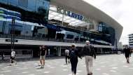 Spectators walk past Rod Laver Arena as qualifying matches for the Australian Open tennis championship continue in Melbourne, Australia, Friday, Jan. 17, 2020. The season's opening Grand Slam event begins here Monday Jan. 20. (AP Photo/Mark Baker)