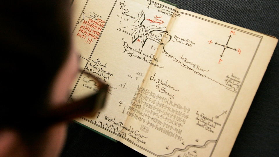 Joy Asfar, of the auction house Bonhams, examines a copy of the 1937 first issue of the first edition of 'The Hobbit' by author J.R.R. Tolkien. (AP Photo/Sang Tan)