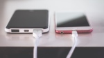Two kinds of smartphone charging cables are plugged in. (Pexels/Steve Johnson)