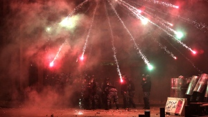 Anti-government protesters use fireworks against Lebanese riot police during a protest at a road leading to the parliament building in Beirut, Lebanon, Saturday, Jan. 18, 2020. (AP Photo/Hassan Ammar)