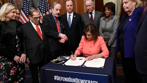 FILE - In this Jan. 15, 2020 file photo, House Speaker Nancy Pelosi of Calif., signs the resolution to transmit the two articles of impeachment against President Donald Trump to the Senate for trial on Capitol Hill in Washington. (AP Photo/Susan Walsh)
