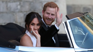 FILE - In this Saturday, May 19, 2018 file photo the Duke and Duchess of Sussex, Meghan Markle and Prince Harry, leave Windsor Castle in a convertible car after their wedding in Windsor, England, to attend an evening reception at Frogmore House, hosted by the Prince of Wales. (Steve Parsons/pool photo via AP, File)