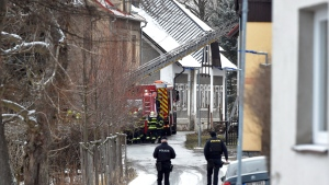 Firefighters stand in front of a house, where eight people with mental and combined impairment were died and another three were seriously injured in the fire on Sunday, Jan. 19, 2020, in Vejprty, Czech Republic. (Slavomir Kubes/CTK via AP)