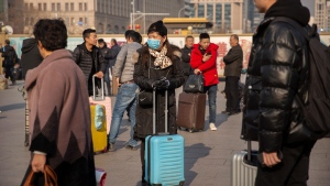 A traveller wears a face mask as she stands near the Beijing Railway Station in Beijing, Friday, Jan. 17, 2020. A second person has died from a new form of coronavirus in central China, health authorities said late Thursday. (AP Photo/Mark Schiefelbein)