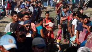 Honduran migrants stand in line for breakfast at a temporary shelter in Tecun Uman, Guatemala in the border with Mexico, Sunday, Jan. 19, 2020. Mexican authorities have closed a border entry point in southern Mexico after thousands of Central American migrants tried to push across a bridge between Mexico and Guatemala. (AP Photo/Moises Castillo)