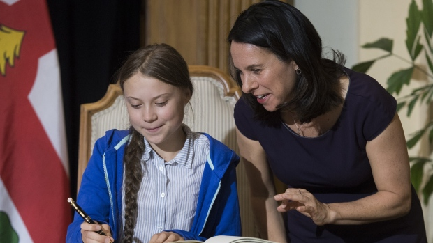 "Swedish climate activist Greta Thunberg, left, signs the Golden Book next to Montreal Mayor Valerie Plante during a ceremony in Montreal, Friday, Sept. 27, 2019. The ""Greta effect"" has stirred up a new sense of urgency over climate change, one fed largely by a freshly coined term: flight shame. THE CANADIAN PRESS/Graham Hughes"