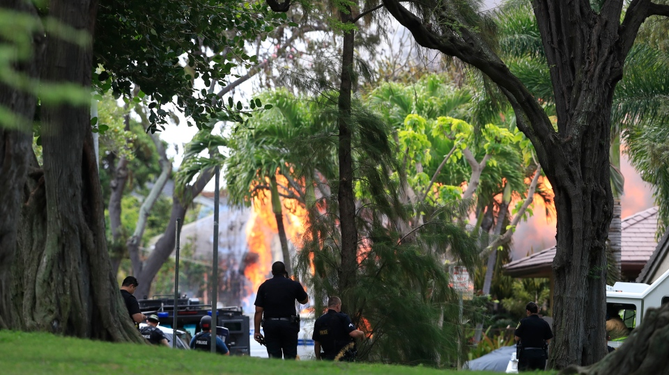 Honolulu police watch a house fire after a shooting and domestic incident at a residence on Hibiscus Road near Diamond Head on Sunday, Jan. 19, 2020, in Honolulu. (Jamm Aquino/Honolulu Star-Advertiser via AP)