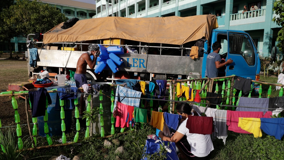 Evacuees do their morning chores at an evacuation center near Taal volcano in Tagaytay, Cavite province, southern Philippines on Sunday, Jan. 19, 2020.  (AP Photo/Aaron Favila)