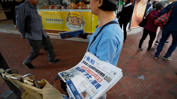 """A vendor gives out copies of newspaper with a headlines of """"Wuhan break out a new type of coronavirus, Hong Kong prevent SARS repeat"""" at a street in Hong Kong, Saturday, Jan. 11, 2020. The federal Public Health Agency says it believes Canadians are at low risk of contracting a new type of pneumonia that has killed one person and has made dozens sick in central China, but it has issued a warning to travellers to and from the city of Wuhan. THE CANADIAN PRESS/AP-Andy Wong"""