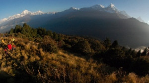 In this Oct. 24, 2014, file photo, trekkers watch the sun rise over the Annapurna Range, right, in central Nepal, as viewed from Poon Hill, above the village of Ghorepani. An avalanche swept the popular Annapurna circuit trekking route, which encircles Mount Annapurna, leaving at least four South Koreans and three Nepali guides missing, authorities said Saturday, Jan. 18, 2020. (AP Photo/Malcolm Foster, File)