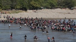 Central American migrants cross the Suchiate River by foot from Tucun Uman, Guatemala, to Mexico, Monday, Jan. 20, 2020. More than a thousand Central American migrants hoping to reach United States marooned in Guatemala are walking en masse across a river leading to Mexico in an attempt to convince authorities there to allow them passage through the country. (AP Photo/Moises Castillo)