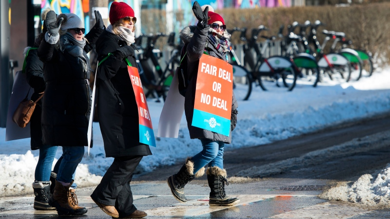 Teachers of the Elementary Teachers' Federation of Ontario wave to honking cars as they participate in a full withdrawal of services strike in Toronto on Monday, January 20, 2020. THE CANADIAN PRESS/Nathan Denette
