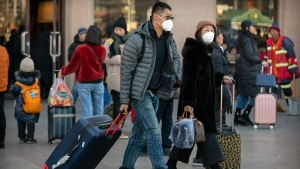 Travelers wear face masks as they walk outside of the Beijing Railway Station in Beijing, Monday, Jan. 20, 2020. (AP Photo/Mark Schiefelbein)