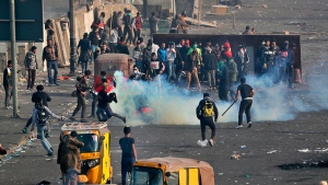 Anti-government protesters take cover while security forces use tear gas during clashes in central Baghdad, Iraq, Monday, Jan. 20, 2020. Iraqi security forces fired tear gas and live rounds during clashes with anti-government protesters overnight and on Monday morning in Baghdad, killing three and wounding dozens of demonstrators, officials said. (AP Photo/Khalid Mohammed)