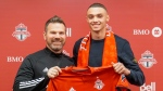 Rocco Romeo and coach Greg Vanney hold up a Toronto FC jersey at the team's training facility in Toronto, Monday, Jan.20, 2020. The MLS club has signed the defender to a contract as a homegrown player.THE CANADIAN PRESS/HO-Toronto FC MANDATORY CREDIT