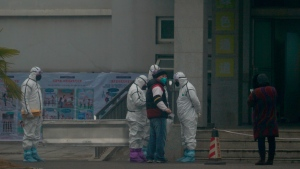 Staff in biohazard suits hold a metal stretcher by the in-patient department of Wuhan Medical Treatment Center, where some infected with a novel coronavirus are being treated, in Wuhan, China, Tuesday, Jan. 21, 2020. Heightened precautions were being taken in China and elsewhere Tuesday as governments strove to control the outbreak of the coronavirus, which threatens to grow during the Lunar New Year travel rush. (AP Photo/Dake Kang)
