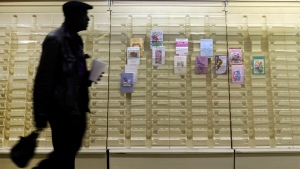 In this April 27, 2013 photo, a man walks past a greeting cards display case in a market. Carlton Cards and Papyrus closing 79 stores in Canada (File/AP Photo/Patrick Semansky)