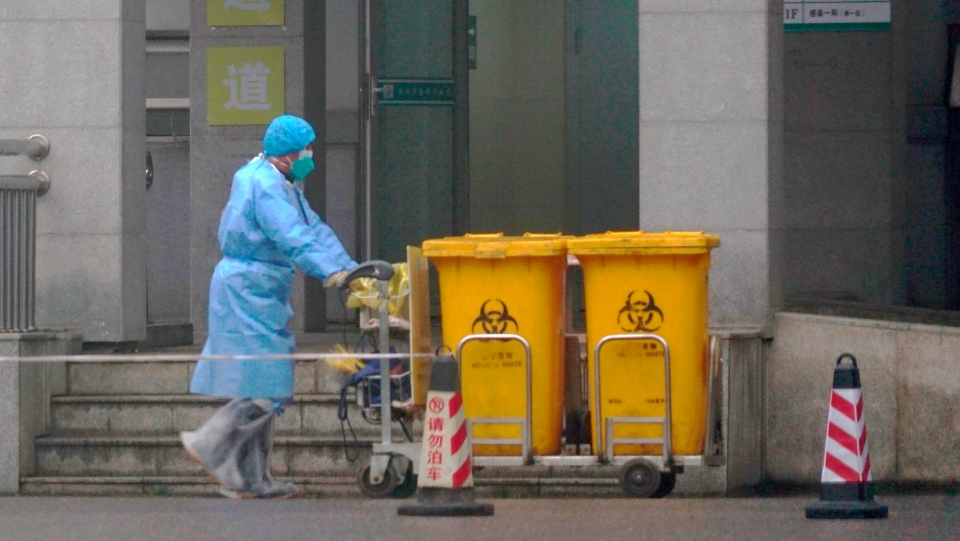 Staff move bio-waste containers past the entrance of the Wuhan Medical Treatment Center, where some infected with a new virus are being treated, in Wuhan, China, Wednesday, Jan. 22, 2020. (AP Photo/Dake Kang)