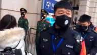 In this image made from video, security officials stand outside the Hankou Railway Station shortly before it was closed in Wuhan in central China's Hubei Province, Thursday, Jan. 23, 2020. China closed off a city of more than 11 million people Thursday in an unprecedented effort to try to contain a deadly new viral illness that has sickened hundreds and spread to other cities and countries in the Lunar New Year travel rush. (Thepaper via AP)