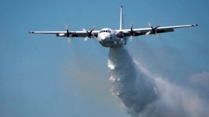 "In this undated photo released from the Rural Fire Service, a C-130 Hercules plane called ""Thor"" drops water during a flight in Australia. Officials in Australia on Thursday, Jan. 23, 2020, searched for a water tanker plane feared to have crashed while fighting wildfires. (RFS via AP)"