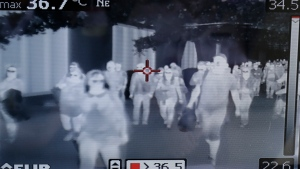 A thermal scanner checks on arriving passengers at Manila's international airport, Philippines, Thursday, Jan. 23, 2020. The government is closely monitoring arrival of passengers as a new coronavirus outbreak in Wuhan, China has infected hundreds and caused deaths in that area. (AP Photo/Aaron Favila)