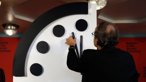 FILE -- Robert Rosner, chairman of the Bulletin of the Atomic Scientists, right, joined by Bulletin of the Atomic Scientists member Lawrence Krauss, left, moves the minute hand of the Doomsday Clock to two minutes to midnight during a news conference at the National Press Club in Wshington, Thursday, Jan. 25, 2018. ( AP Photo/Carolyn Kaster)