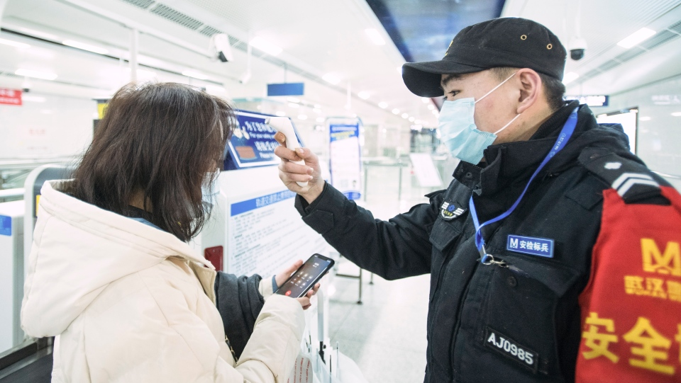 In this photo released by China's Xinhua News Agency, an official checks a passenger's temperature at a subway station in Wuhan in central China's Hubei Province, early Thursday, Jan. 23, 2020. (Xiao Yijiu/Xinhua via AP)