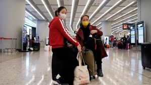 Passengers wear masks to prevent an outbreak of a new coronavirus in the high speed train station, in Hong Kong, Wednesday, Jan. 22, 2020. The first case of coronavirus in Macao was confirmed on Wednesday, according to state broadcaster CCTV. The infected person, a 52-year-old woman, was a traveller from Wuhan. (AP Photo/Kin Cheung)