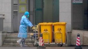 In this Wednesday, Jan. 22, 2020, file photo, staff move bio-waste containers past the entrance of the Wuhan Medical Treatment Center, where some infected with a new virus are being treated, in Wuhan, China. The number of cases of a new coronavirus from Wuhan has risen over 400 in China Chinese health authorities said Wednesday. (AP Photo/Dake Kang, File)