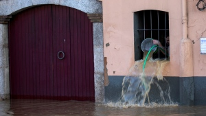 A man removes water from his house during flooding following a storm in Girona, Spain, on Thursday, Jan. 23, 2020. At least 11 have died and five people remained missing on Thursday following a calamitous storm that has caused rivers to overflow and sea waters to inundate vast agricultural areas in eastern Spain. (AP Photo/Emilio Morenatti)